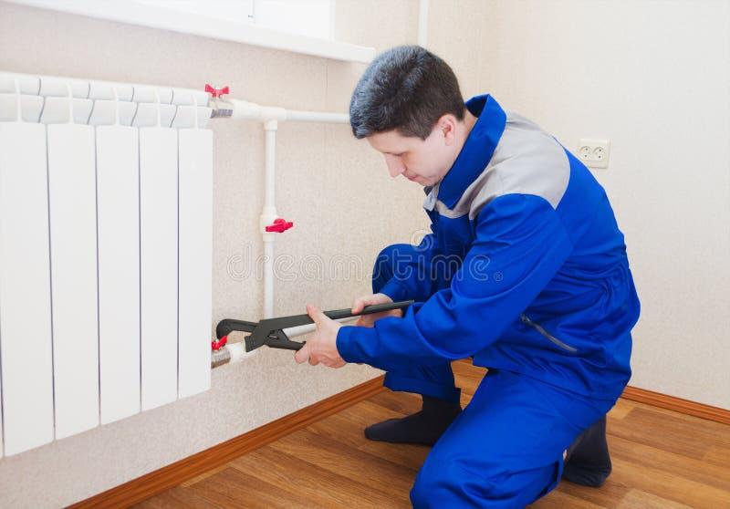 Een loodgieter voert de installatie van radiator het verwarmen uit royalty-vrije stock fotografie