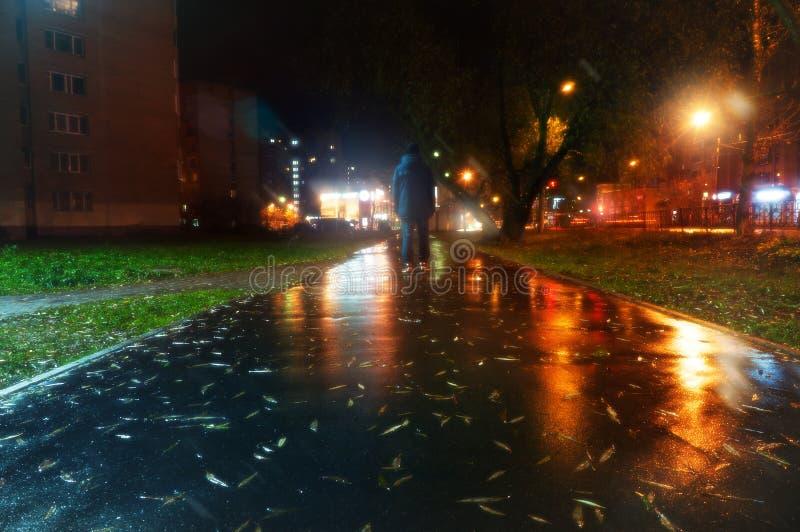 Een loopt de geheimzinnige mensentribunes alleen in de straat, onder auto's in een lege stad, weat weg na de regen, de nachtstraa royalty-vrije stock foto's