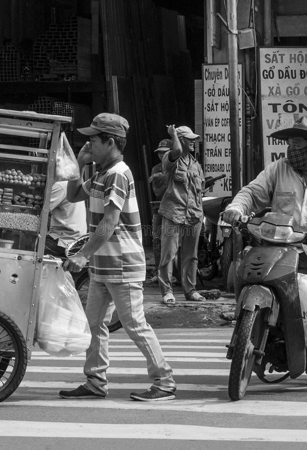 Een lopende verkoper gaat over door aangezien de mensen in een straat van Ho Chi Minh City, Vietnam omzetten stock fotografie