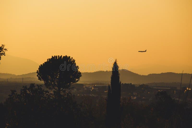 Een low-flying vliegtuig en de bergen worden gesilhouetteerd bij schemer stock foto's