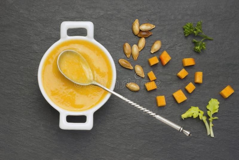 Een luchtfoto van de soep van de pompoenroom met peterselie in de witte ceramische kom Pompoenpuree met kruiden, uitstekende zilv stock fotografie