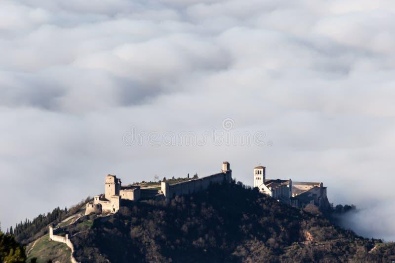 Een luchtfoto van de stad Assisi en de kerk van St. Francis over een zee van mist stock fotografie