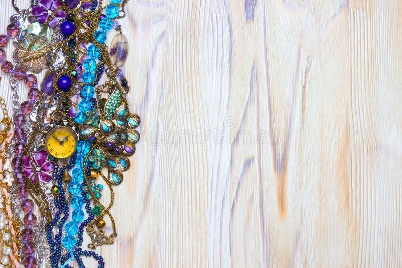 Een luchtfoto van leuke lilac natuurlijke violetkleurige parels, stenen, kristallen en halsbanden op de houten lijst Veelkleurige royalty-vrije stock foto's