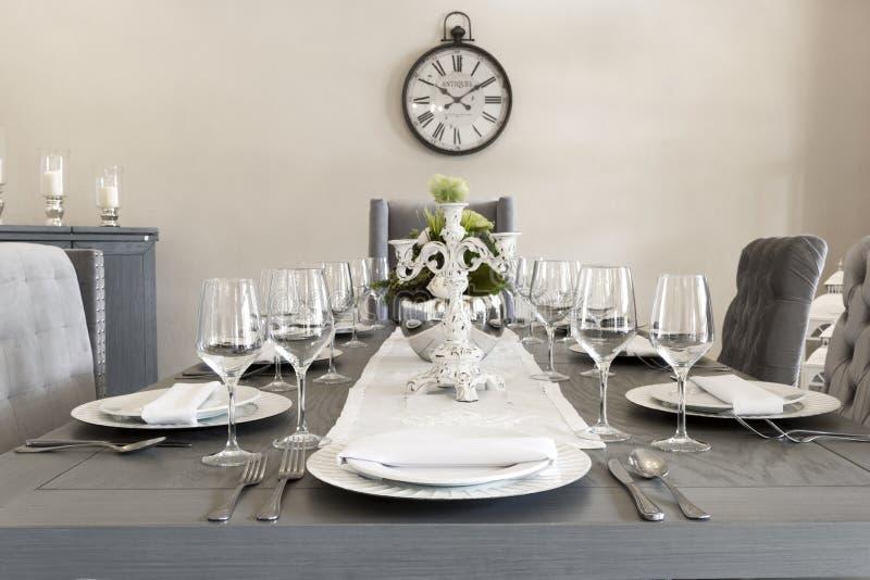 Een luxueuze eetkamer van een huis met glazen en platen royalty-vrije stock foto's