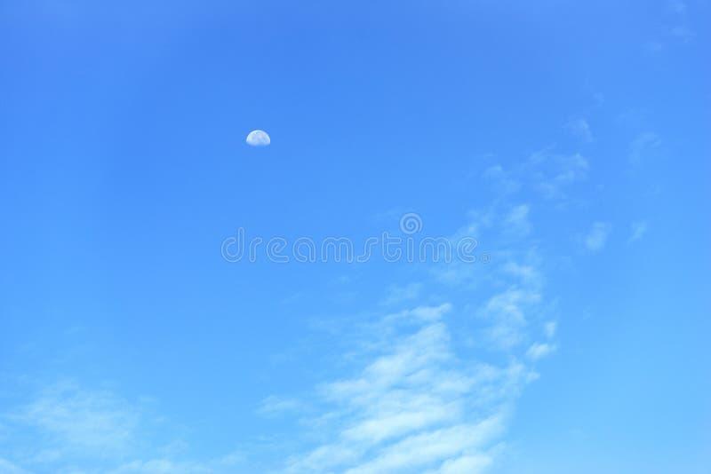 Een maan op blauwe hemel met witte wolken stock foto's