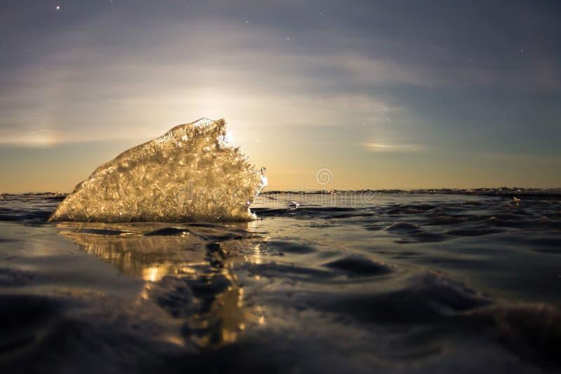 Een maanhalo die door de transparante ijsrand glanzen, Olkhon-eiland, Meer Baikal stock foto