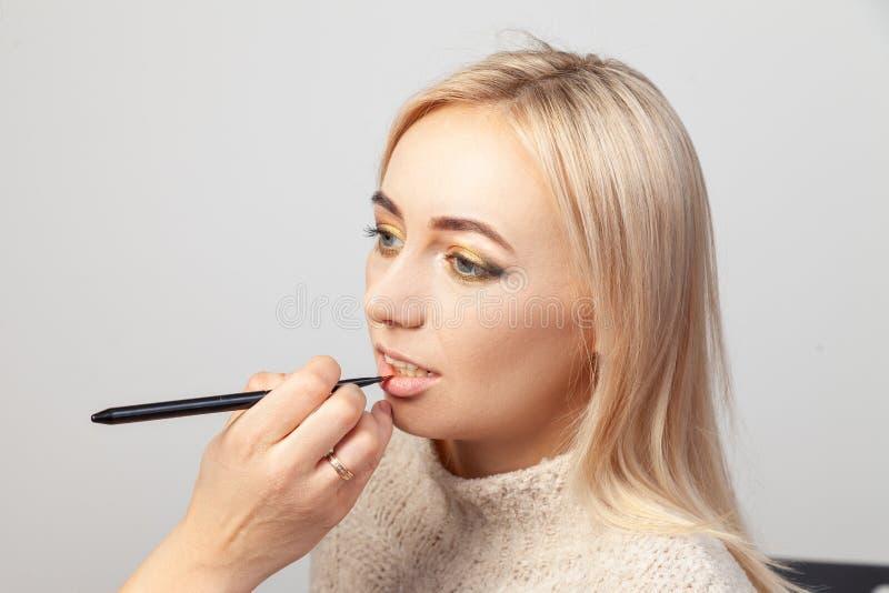 Een make-up in een schoonheidsstudio, een grimeur met een borstel in haar hand zet een product op de lippen van een blondemodel m stock afbeeldingen