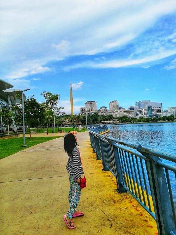 Een Maleisisch meisje die zich bij het meer bevinden, die de bewolkte hemel in Precint 8, Putrajaya Maleisië bekijken stock afbeelding