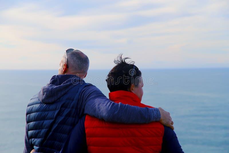 Een man in een blauw vest koestert een vrouw in een rood vest tegen de achtergrond van de oceaan en de hemel royalty-vrije stock foto's