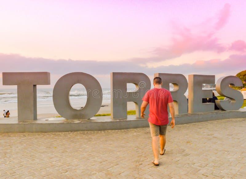 Een man die loopt, met zijn rug naar de camera In Torres, Brazilië royalty-vrije stock foto's