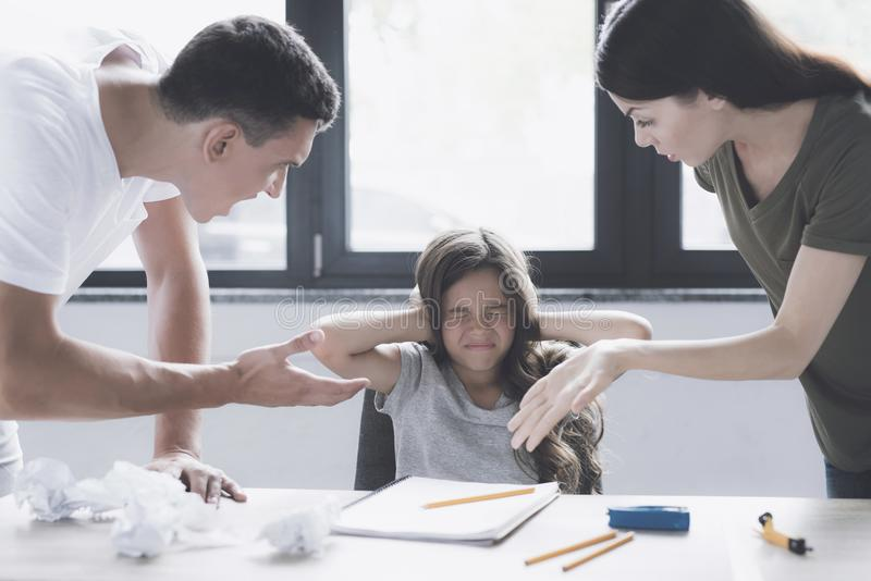 Een man en een vrouw berispen een klein meisje dat naast hem bij de lijst zit, die haar oren behandelen met haar handen royalty-vrije stock afbeeldingen