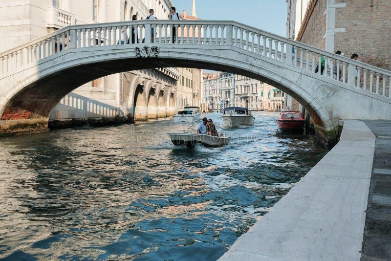 Een man en een vrouw drijven op een kleine boot onder een brug in Venetië royalty-vrije stock afbeeldingen