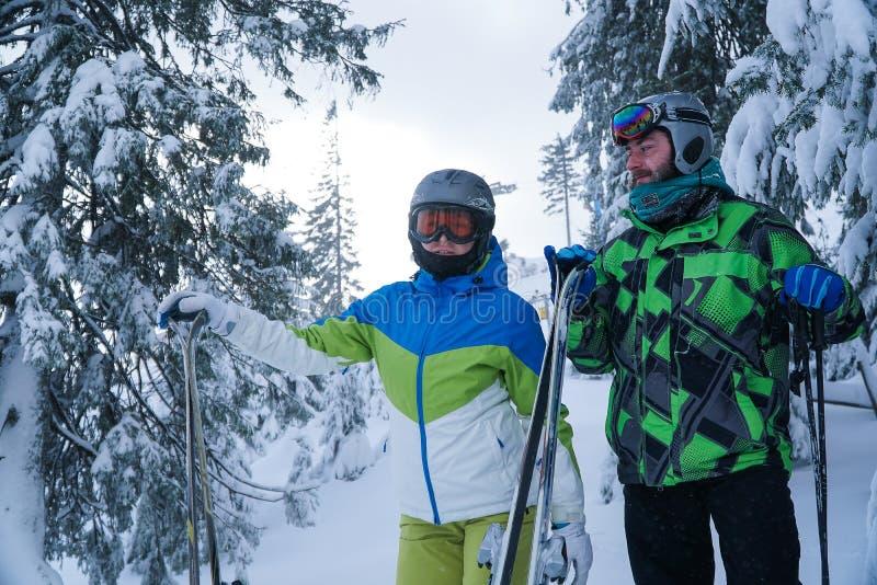 Een man en een vrouw gaan ski?end De bergen van de de wintersneeuw stock foto