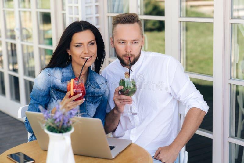 Een man en een vrouw gingen zitten om in een koffie te ontspannen, drinkend cocktails door stro Een mens werkt achter zijn laptop royalty-vrije stock fotografie