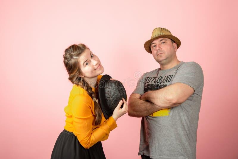 Een man en een vrouw in een hoed op een roze achtergrond, het concept gezinsverhoudingen tussen echtgenoot en vrouw stock fotografie