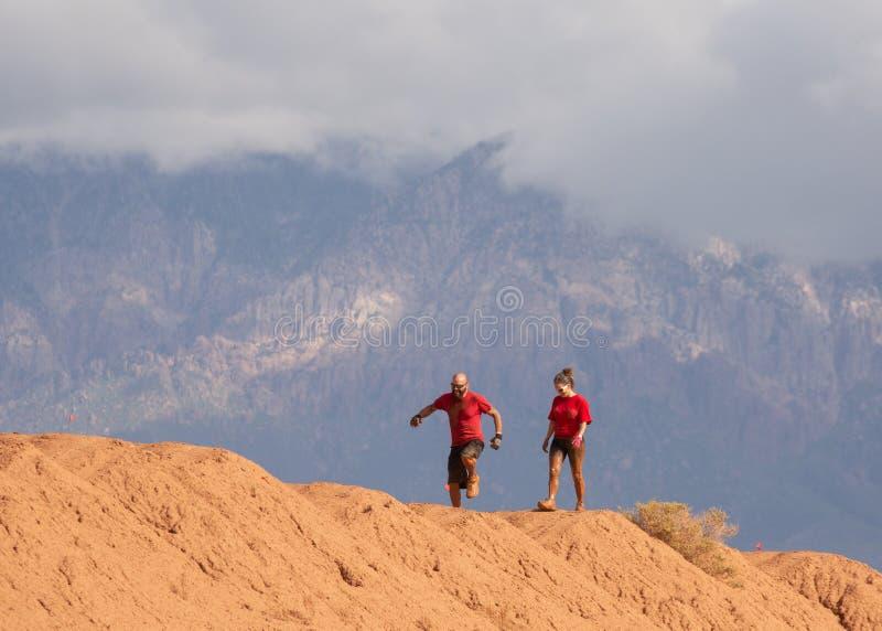 Een man en een vrouw kruisen een rand van rood vuil tijdens een de hinderniscursus van de modderlooppas met bergen en wolken in d stock fotografie