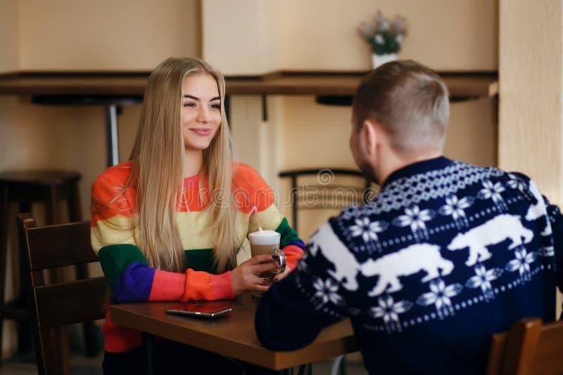 Een man en een vrouw zitten in een koffie en het drinken de koffie, een paar draagt buitensporige sweaters, glimlacht een meisje, stock fotografie