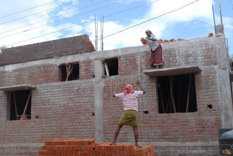 Een man en vrouwen die in een bouwwerf werken royalty-vrije stock afbeelding