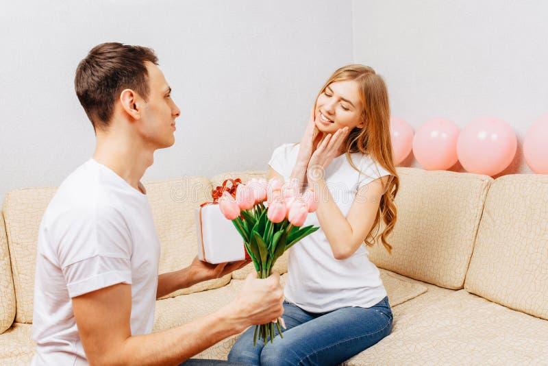 Een man geeft een boeket van tulpen en een gift thuis aan een vrouwenzitting op de bank, concept de dag van vrouwen royalty-vrije stock afbeelding