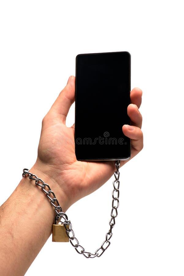 Een man hand wordt gebonden aan een smartphone door een ketting Geïsoleerdj op witte achtergrond Het concept hangt van technologi royalty-vrije stock foto's