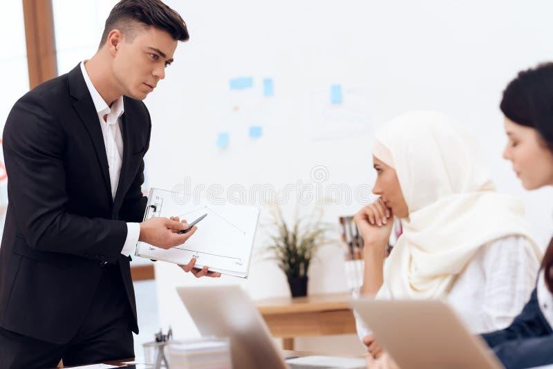 Een man maakt tot een eis aan een vrouw die een hijab dragen royalty-vrije stock fotografie