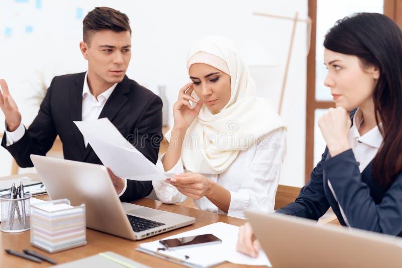 Een man maakt tot een eis aan een vrouw die een hijab dragen stock afbeelding