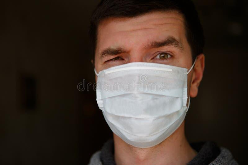 Een man in een medisch masker tijdens een coronavirus-epidemie kijkt naar het kader en wijst op de noodzaak van een masker royalty-vrije stock afbeeldingen