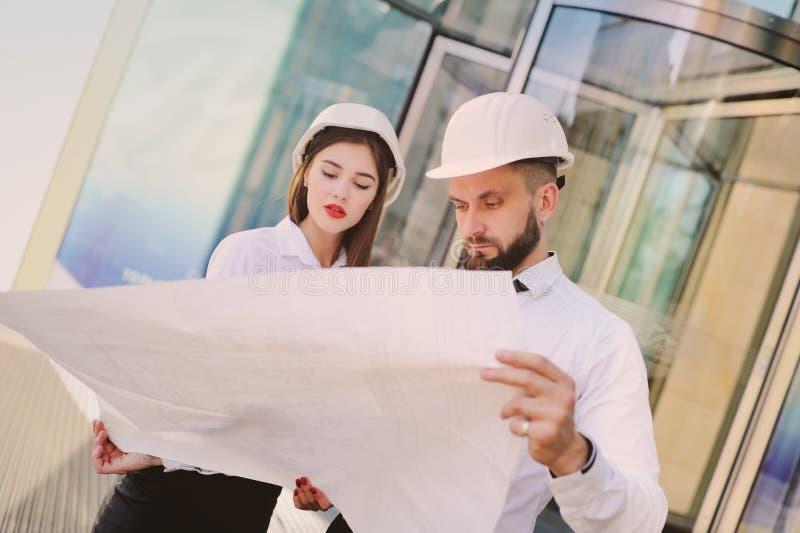 Een man met een baard en een vrouw in bedrijfskleren bestudeert tekeningen en documenten voor een nieuw project royalty-vrije stock foto's