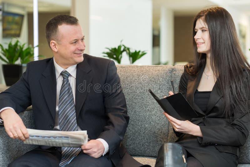 Een man met krant en vrouwen met blocnote het spreken royalty-vrije stock afbeelding