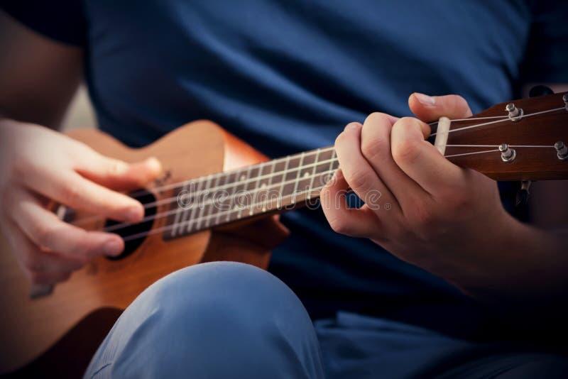 Een man speelt een vrolijke melodie op de ukulele royalty-vrije stock fotografie