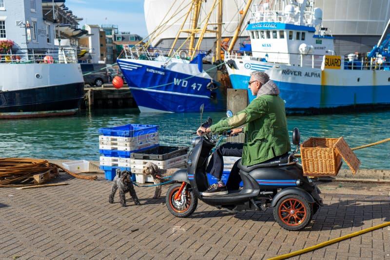 Een man van middelbare leeftijd op een mobiliteitscooter die zijn hond neemt voor een wandeling op de kade of het dok royalty-vrije stock foto