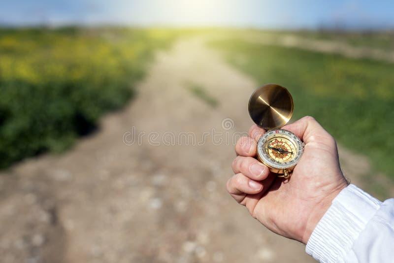 Een man zoekt het noorden in het veld met een kompas royalty-vrije stock foto