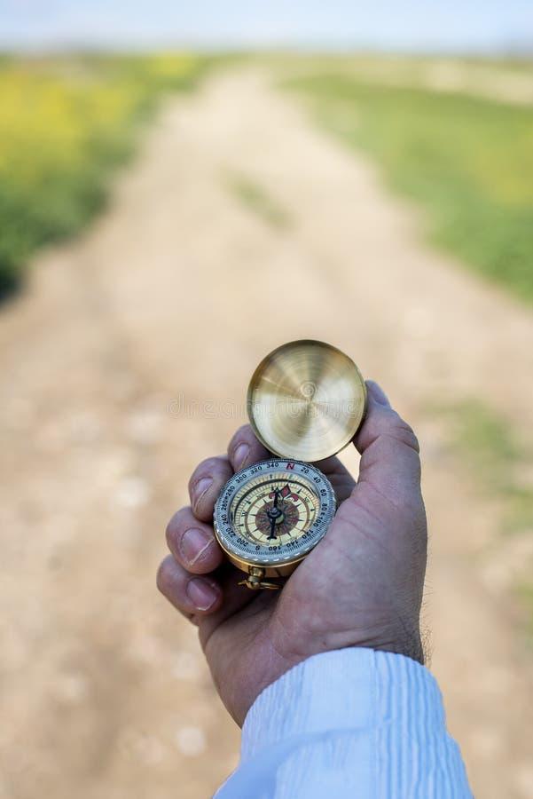Een man zoekt het noorden in het veld met een kompas stock foto's