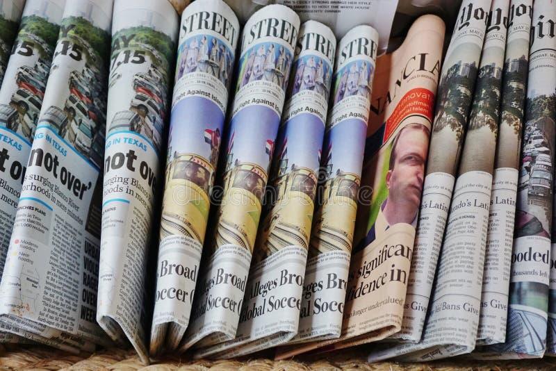 Een mand van gevouwen Engelstalige kranten stock afbeeldingen