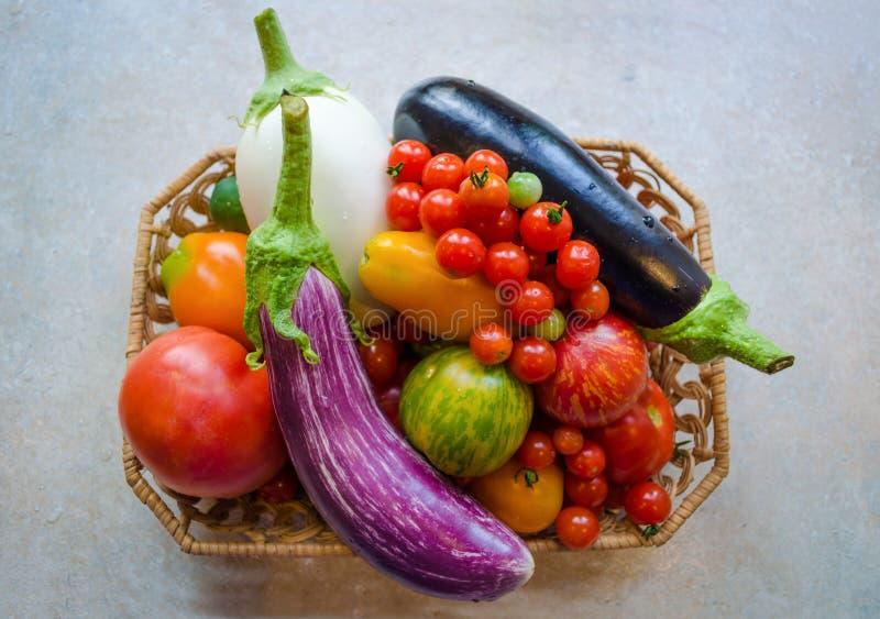 Een mandhoogtepunt van verse rijpe organische groenten - aubergines en tomaten, royalty-vrije stock foto's