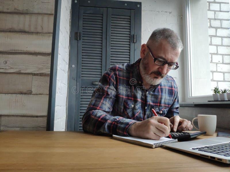 Een mannelijke accountant werkt thuis bij een computer, drinkt koffie en bekijkt een laptop monitor royalty-vrije stock foto's