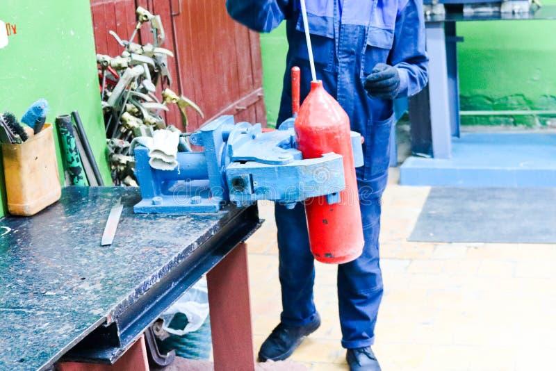 Een mannelijke arbeider op een grote metaal industriële ondeugd herstelt een rode brandblusapparaatcilinder in een workshop bij d royalty-vrije stock foto