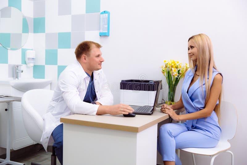 Een mannelijke arts in professionele kleren adviseert een jonge vrouwenpatiënt in een kliniek Paar die in het bureau spreken royalty-vrije stock foto's