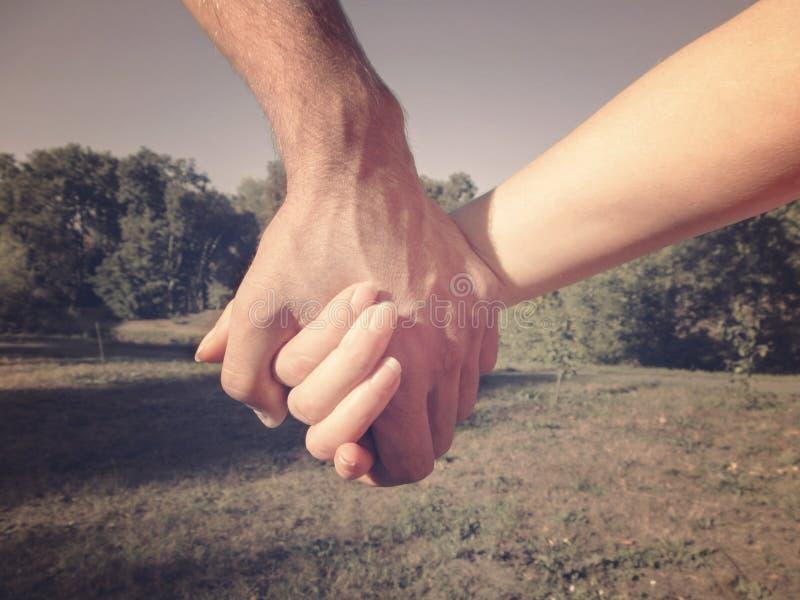 Een mannelijke hand houdt een vrouwelijke hand tegen een achtergrond van aard Paar op de handen van een gangholding, het concept  royalty-vrije stock afbeeldingen