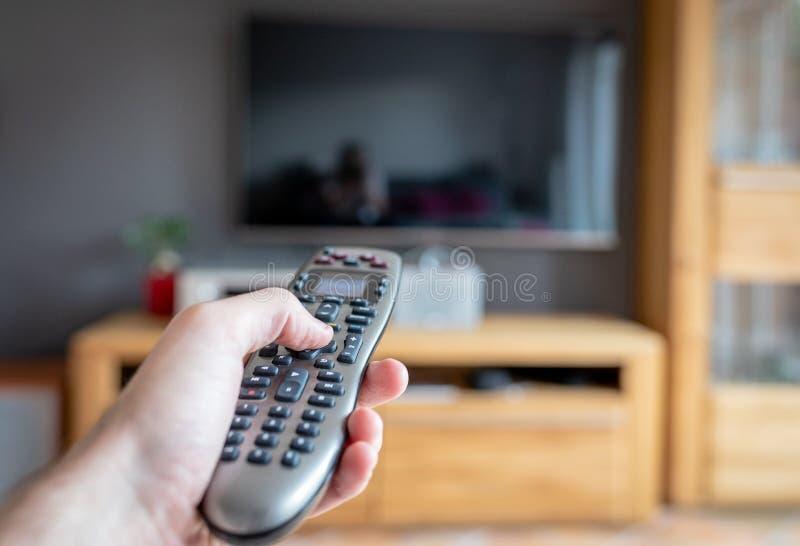 Een mannelijke hand een moderne afstandsbediening houden die richtend aan TV royalty-vrije stock fotografie