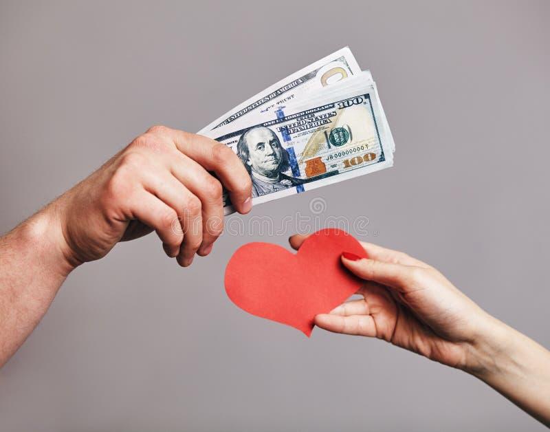 Een Mannelijke hand een pak van geld houden die proberend om rode harten van vrouwelijke hand te kopen - het Kopen liefdeconcept stock afbeeldingen