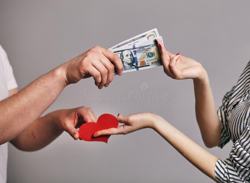 Een Mannelijke hand een pak van geld houden die proberend om rode harten van vrouwelijke hand te kopen - het Kopen liefdeconcept royalty-vrije stock foto