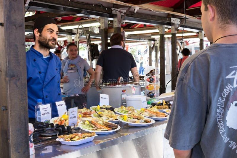 Een mannelijke kok die gebraden vissenvoedsel verkopen in Bergen fishmarket, Noorwegen royalty-vrije stock foto