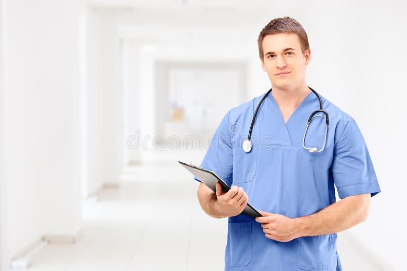 Een mannelijke medische arts in een eenvormige holding een klembord en een posin royalty-vrije stock foto