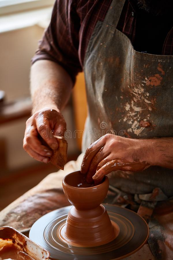 Een mannelijke pottenbakker in schortvormen werpt van klei, selectieve nadruk, close-up royalty-vrije stock afbeelding