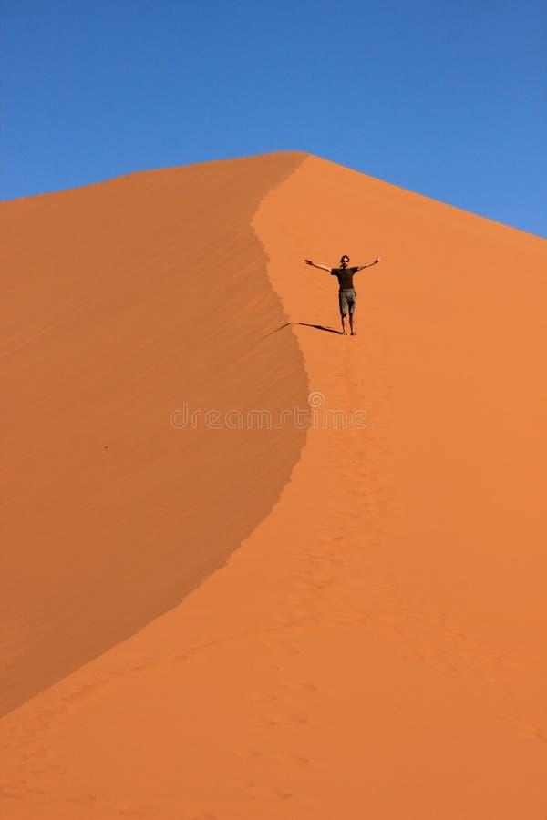 Een mannelijke reiziger in sportkleding bevindt zich op het oranje zand van een duin in het Nationale Park van Sosusfle stock foto's