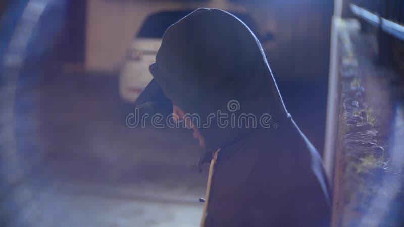 Een mannelijke rover, bedreigt een vrouw en neemt haar beurs, in een donkere steeg bij nacht royalty-vrije stock afbeeldingen