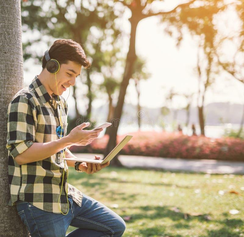 Een mannelijke student en het luisteren muziek die gezet op een gras in het stadspark ontspannen royalty-vrije stock foto's