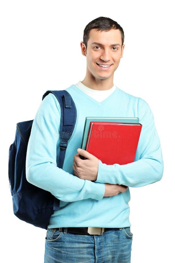 Een mannelijke student met de boeken van een schooltasholding stock afbeeldingen