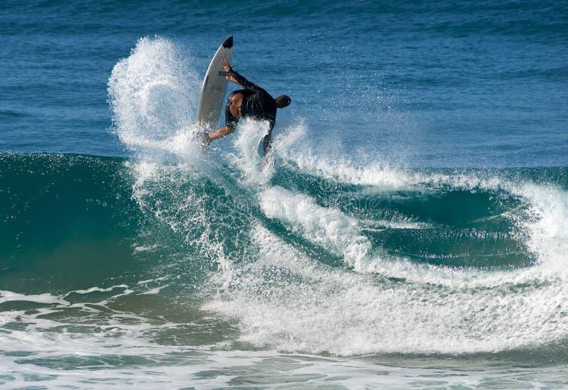 Een mannelijke surfer die een golf met acrobatische stijl weggaan stock fotografie